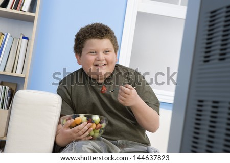 Smiling overweight boy eating bowl of fruit in front of television - stock photo