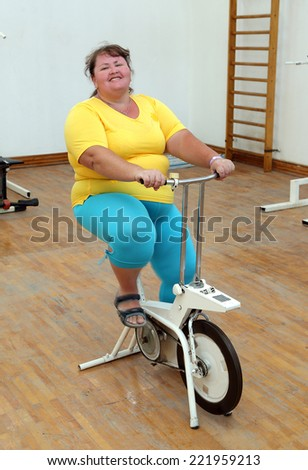 smiling overweight woman exercising on bike simulator - stock photo