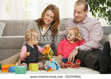 Smiling parents and small daughter looking at baby sitting on floor. - stock photo