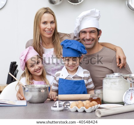 Smiling parents helping children baking cookies in the kitchen - stock photo