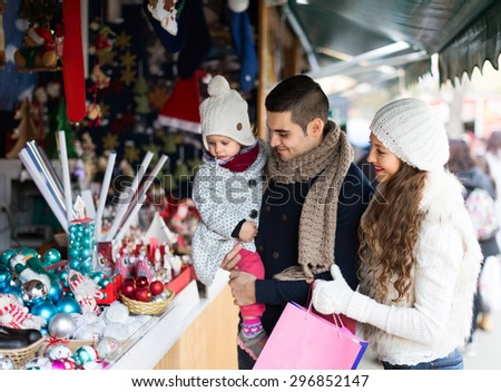 Smiling parents with small daughter at counter of X-mas market - stock photo