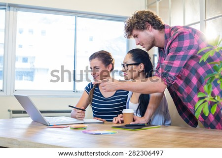 Smiling partners working together on laptop and digitizer in the office - stock photo