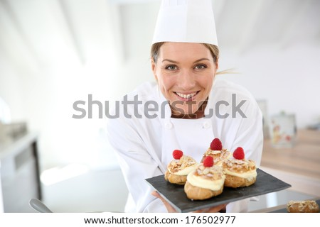 Smiling pastry chef showing desserts on plate - stock photo