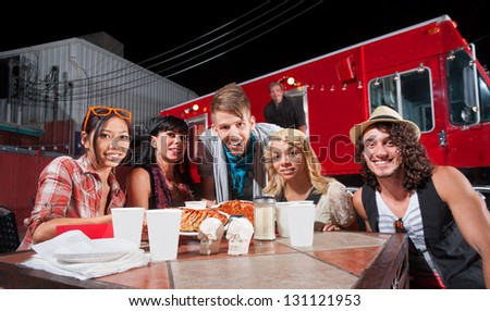 Smiling patrons at table in front of chef and food truck - stock photo