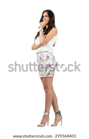 Smiling pensive elegant woman with hand on her chin looking away.  Full body length portrait isolated over white studio background.  - stock photo
