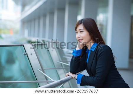 Smiling pensive Japanese business lady standing outdoors - stock photo