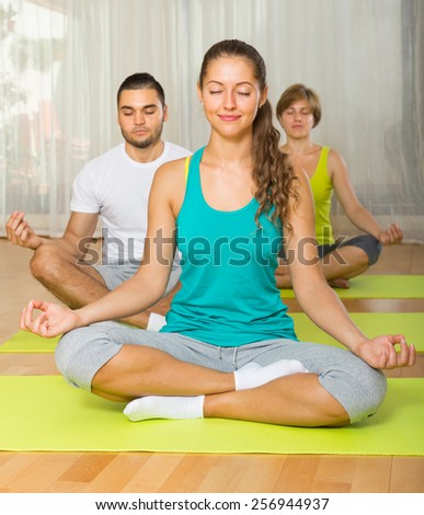 smiling people  having yoga class in sport club - stock photo
