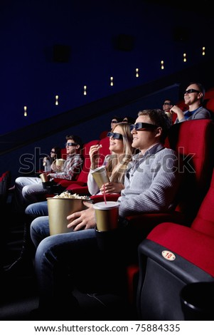 Smiling people in 3D glasses in cinema - stock photo