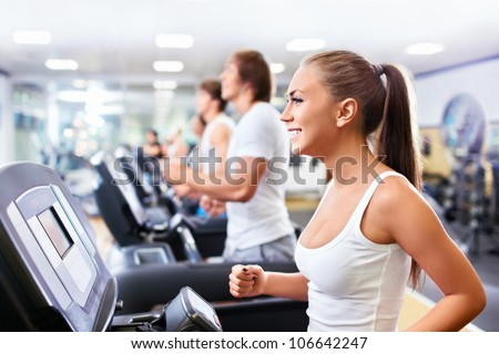 Smiling people on treadmills - stock photo