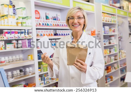 Smiling pharmacist holding prescription and envelope in the pharmacy - stock photo