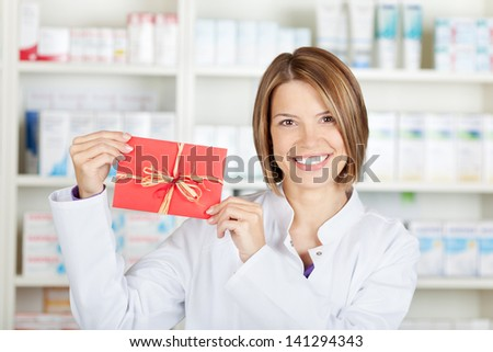 Smiling pharmacist showing a red card at the drugstore - stock photo