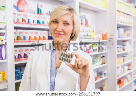 Smiling pharmacist showing blister in the pharmacy - stock photo