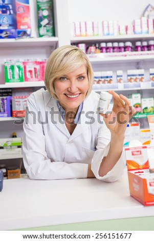 Smiling pharmacist showing medication in the pharmacy - stock photo