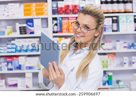 Smiling pharmacist using tablet pc at the hospital pharmacy - stock photo