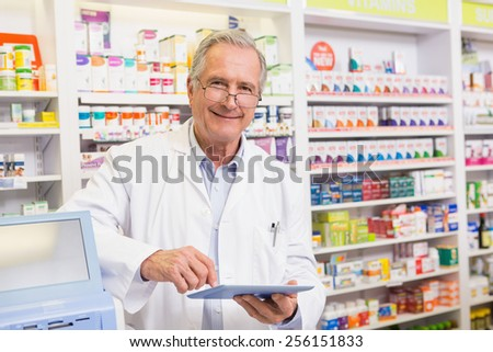 Smiling pharmacist using tablet pc in the pharmacy - stock photo