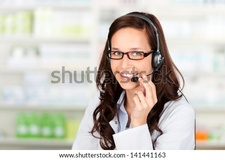 Smiling pharmacist wearing headset at the drugstore - stock photo