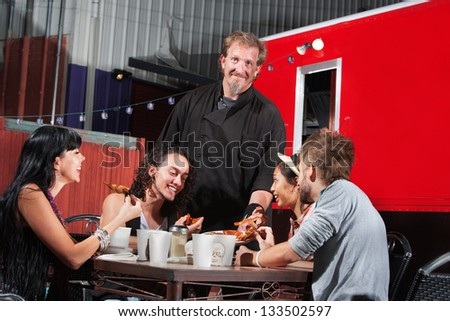 Smiling pizza canteen owner with happy customers - stock photo