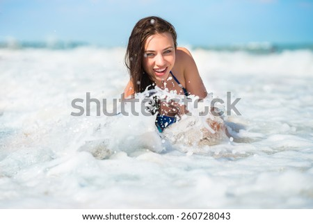 Smiling playful brunette posing in the water - stock photo