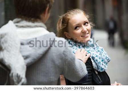 Smiling playful girl flirting with young guy at the street - stock photo
