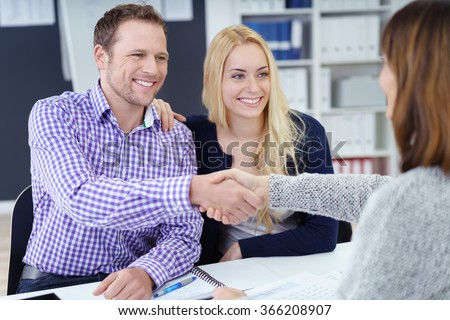 Smiling pleased attractive young couple shaking hands with a business broker or adviser as they sit with her in the office in a meeting, view over the advisers shoulder - stock photo