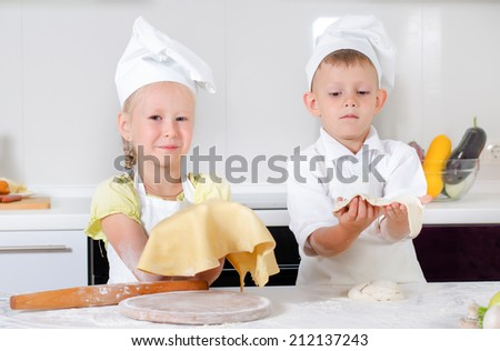 Smiling pleased little girl dressed in an apron and chefs cap holding up her thinly rolled out pastry for a pizza base with a proud smile watched by her young brother - stock photo