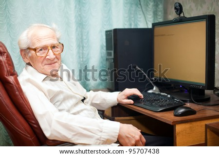 smiling pleased old man sitting near computer - he is working - stock photo