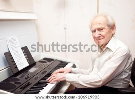smiling pleased senior man playing piano - stock photo