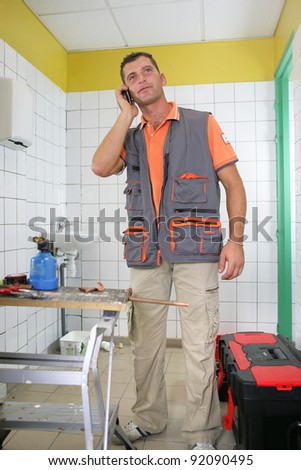 Smiling plumber on the phone - stock photo