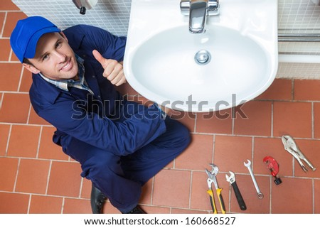 Smiling plumber repairing sink showing thumb up in public bathroom - stock photo