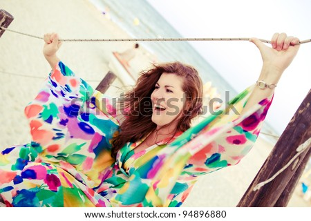 Smiling plus size model is holding line at the beach. - stock photo