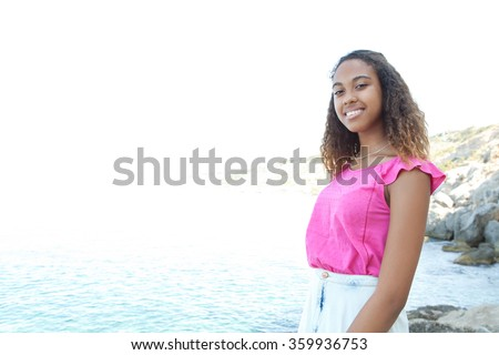 Smiling portrait of a beautiful joyful african american adolescent girl looking at camera. relaxing on a rocky coast beach with sky, outdoors lifestyle. Travel and healthy living, nature exterior. - stock photo