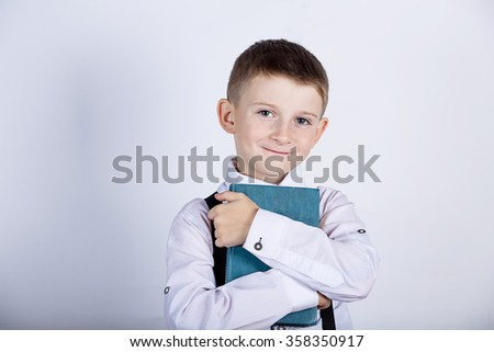 Smiling Portrait of a cute little school boy loving to learn, holding with hands a book and wearing glasses isolated over yellow background.  - stock photo