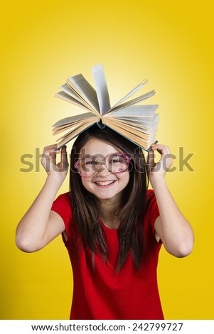Smiling Portrait of a cute little schoolgirl loving to learn holding with hands open book on her head,wearing glasses isolated over yellow background.  - stock photo