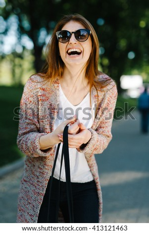 smiling portrait of an attractive cute beautiful caucasian girl with little bag in her hand enjoy warm spring sunset  - stock photo