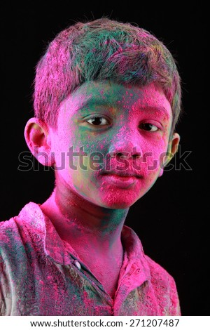 Smiling Portrait of boy with face smeared with colored powder in a dark background. Concept for Indian festival Holi. - stock photo