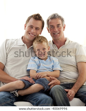 Smiling portrait of son, father and grandfather sitting on sofa - stock photo