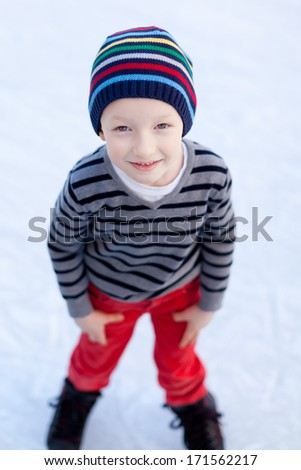smiling positive boy ice skating at winter - stock photo