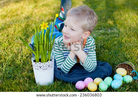 smiling positive boy with flowers and easter eggs at spring time - stock photo