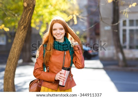 Smiling  positive pretty young woman with beautiful long red hair in leather jacket and scarf holding tumbler of coffee and walking in the street - stock photo
