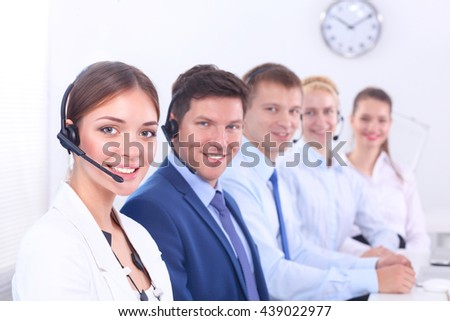 Smiling positive young businesspeople and colleagues in a call center office - stock photo