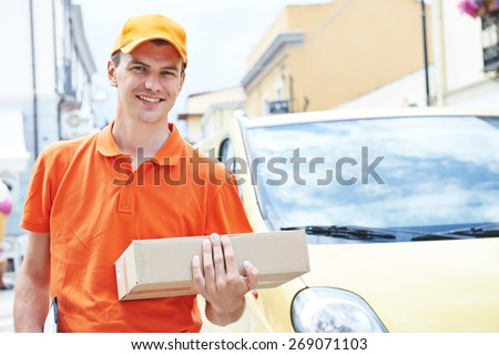 Smiling postal delivery courier man outdoors  in front of cargo van delivering package - stock photo