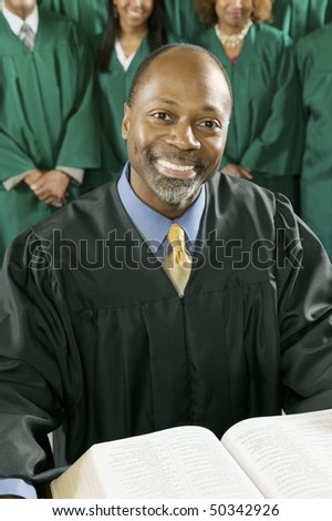 Smiling Preacher with Bible in church, portrait - stock photo