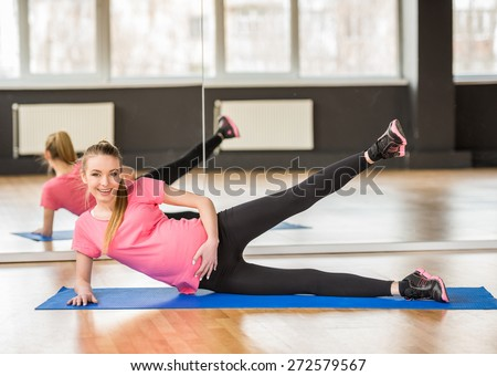Smiling pregnant woman at gym fitness exercise practicing aerobics on mat. - stock photo