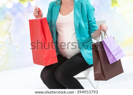 Smiling pregnant woman sitting with shopping bags - stock photo