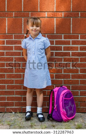 Smiling preschool girl in blue school uniform gingham dress with backpack standing near the brick school wall.  Back to school.  - stock photo