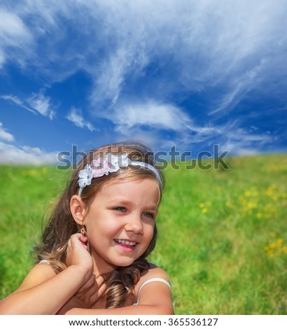 Smiling preschool girl sitting on a summer hill - stock photo