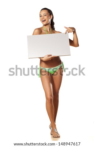 smiling pretty and beautiful young brunette in a bikini holding a blank board on which points a finger - stock photo
