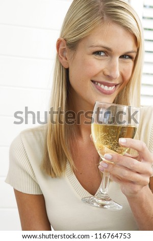 Smiling pretty blonde woman holding a large glass of wine in her hand - stock photo