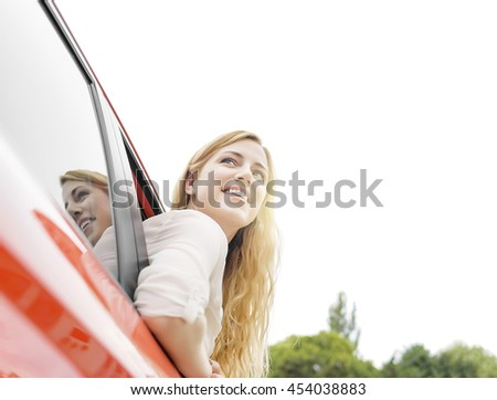Smiling pretty blonde woman in red car. She looks out the car window. - stock photo