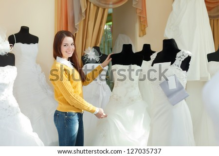 Smiling pretty bride chooses wedding outfit in bridal boutique - stock photo